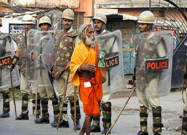 A seer goes about his business in Ayodhya  as police personnel stand guard