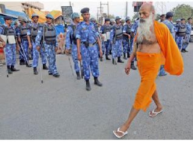 A seer goes about his business in Ayodhya on Saturday, as security personnel stand guard