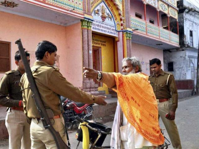Security personnel stop a sadhu on a closed road as prohibitory orders were imposed in Ayodhya